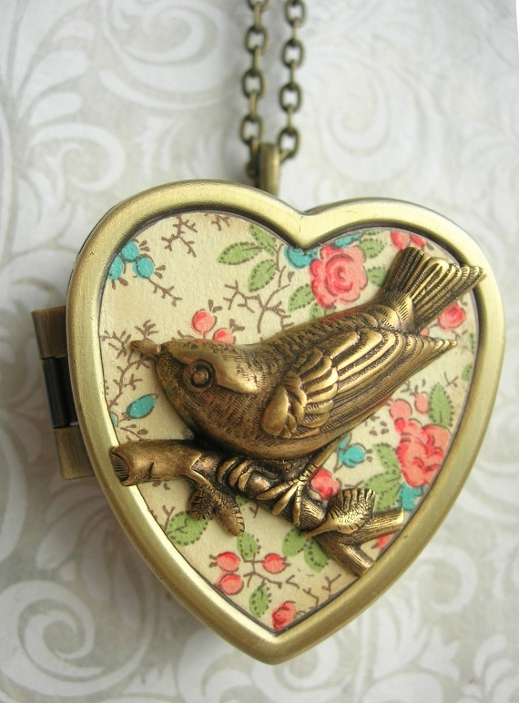 "Little Wing Miniature Music Box Locket  Little Wing hides a clever secret; when the tiny key on the reverse side of this locket is wound, a little music box plays a short tune. An encouraging phrase is inside this locket to shore up the spirits too...""Chin-up, Buttercup""."