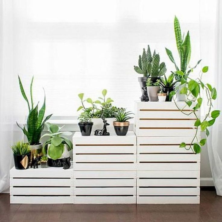 Clearing out the clutter? Looking to make a fresh start? We recommend organizing your space with the clean white lines of this DIY tiered plant stand. It's made from simple wooden storage crates that Wooden Storage Crates, Wooden Boxes, Decoration Plante, Diy Plant Stand, Outdoor Plant Stands, Modern Plant Stand, Creation Deco, Diy Planters, Planter Ideas