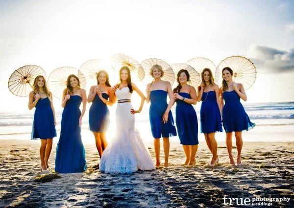 Beachfront Wedding at the Scripps Seaside Forum with I Do Weddings. Blue bridesmaids dresses with white parasols. Beach Wedding. Good lighting - photography.