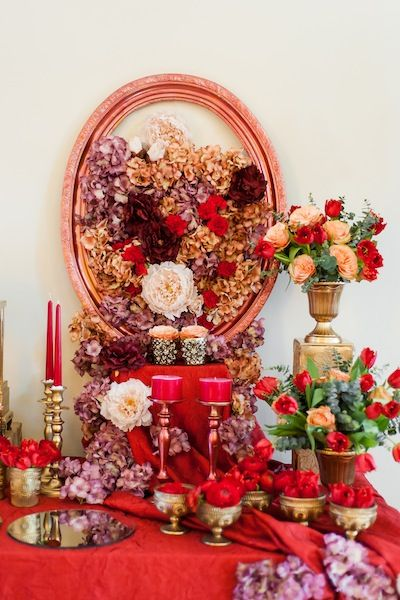 Red composition with roses, artificial flowers, candles, golden chandeliers and a large oval frame.