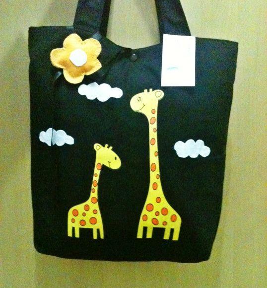 Bolsa de lona com forro de tricoline, estampada de girafa, fechamento com botão de pressão e incluso chaveiro de flor.