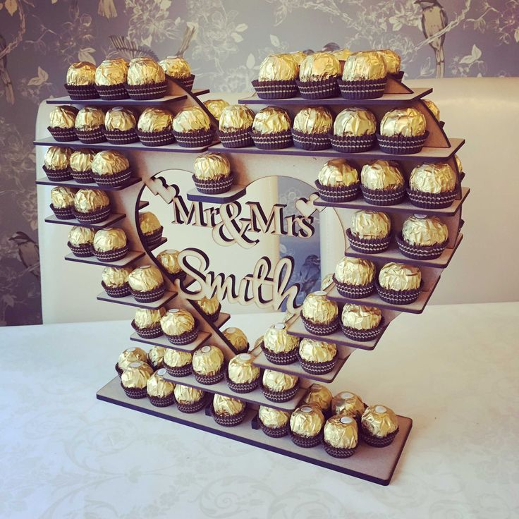 Wooden Heart Ferrero Rocher Stand - Ideal for weddings and events. The size of the heart is approx. 42cm x 36cm and can hold around 100 Ferrero Rocher's . It is made from 6mm thick MDF and simply slots together with shelves both sides of the heart. It is sent flat with glueing recommend. You can...