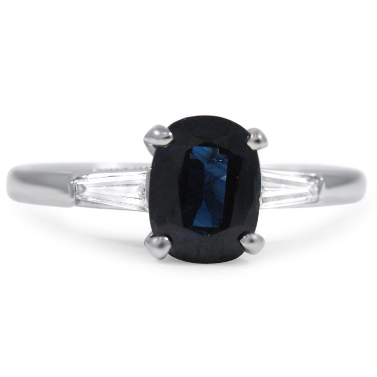 THE SIDNEY RING This classically styled ring showcases a deep blue cushion sapphire complemented on each side by a glimmering tapered diamond baguette accent for a timeless and spectacular piece (approx. 0.16 total carat weight).