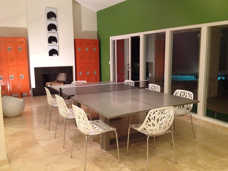 """New living room set up for my house in Palm Springs.  James De Wulf concrete ping pong table, orange Penco lockers, birch sapling white plastic dining chairs, Beatles """"Hard Days Night"""" acrylic art."""