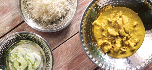 Snijd de kipfilets in stukjes. Giet twee eetlepels arachideolie in een stoofpan, bak de stukjes kip en kruid ze met zout. Als ze eenmaal goudgeel gebakken zijn, haal ze dan uit de pan met een schuimspaan en giet de bakolie weg.      Roer in een kommetje de geschilde en geraspte gember, de kruiden en de gevogeltefond tot een stevig mengsel.      Snipper de uien, hak de look fijn en laat ze in een soeplepel arachideolie (op een matig vuur) stoven in de stoofpan. Voeg de currypasta toe en ...