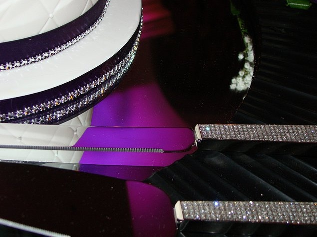 Rhinestone Elements Reinforced .....   The cake detailing included a fine band of rhinestone and therefore the rhinestone handles on the cake knife and server were a natural fit. Note the reflection of the purple uplighting as seen on the serving utensils - makes for an interesting photo.This design done by grandbeginningsdecor