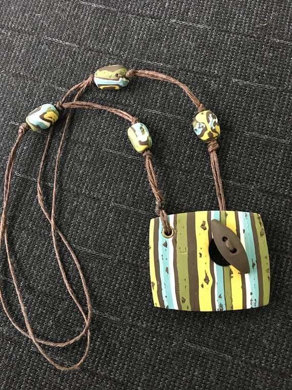 this is a brown, blue, green, and yellow toggle pendant, on a 16 inch cord made with polymer clay matching earrings available