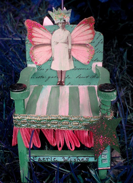 This is a fairy chair I made from a small unfinished wooden chair, paint and found objects. On the back of the chair is a tiny altered art book I made, which is tied closed with silk ribbon.    This is an altered piece in my series of altered art. This