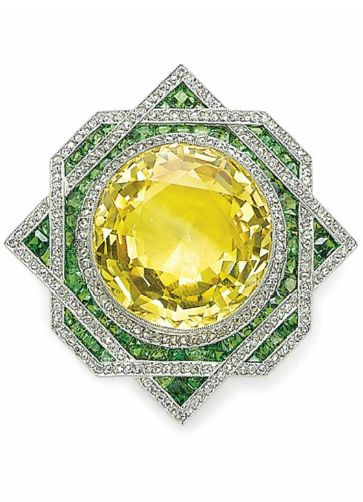BROOCH set with a circular-cut yellow sapphire, trimmed with rose-cut diamonds, within a calibré-cut demantoid garnet and rose-cut diamond overlapping surround, mounted in platinum and gold, circa 1915.