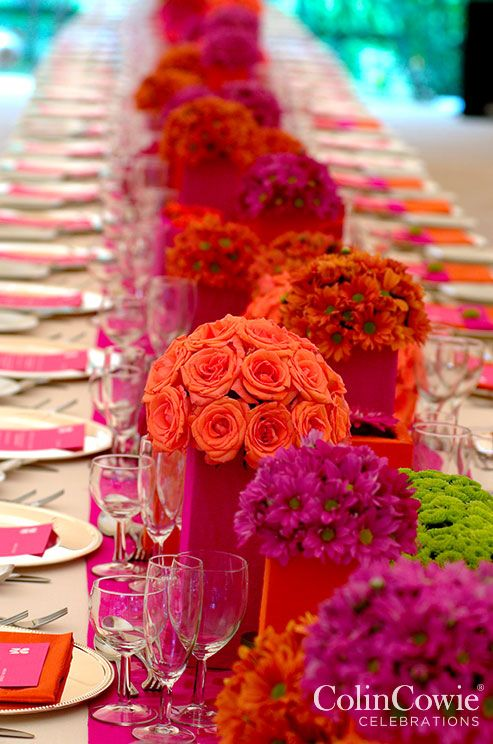 Floral arrangements in bright orange and fuchsia make this table pop. Low Centerpieces, Wedding tabletop, Flowers