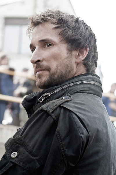 "Noah Wyle portrays the character of Tom Mason in the tv show ""Falling Skies""........"