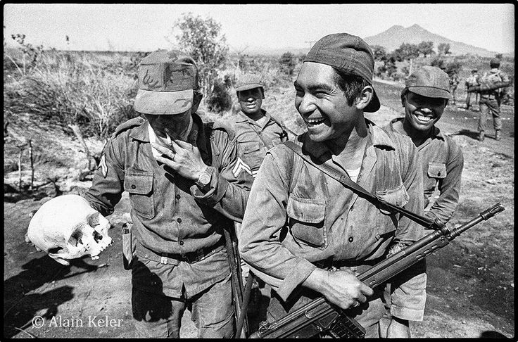 After clashes with guerrilla, Salvadoran soldiers laugh as one of them shows a human skull. Salvadoran Civil War, February 8th, 1982.