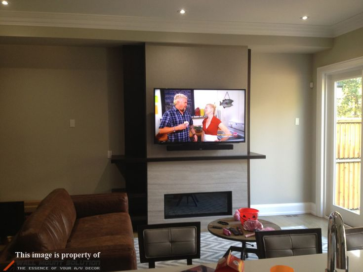55″ Sony LED TV mounted on a custom built-wall with fireplace underneath. Denon DHT-S514 sound bar mounted flush against the TV using sound bar brackets.