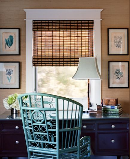 home office/workspace designed by Waterleaf Interiors. Grasscloth wallpaper contrasts w/ the black frames & desk (w/ glass top for added luxury). The beautiful details of the bamboo chair come to life with a coat of turquoise paint, a color repeated in the coral wall art flanking the window. Wooden blind finishes the nature-inspired look