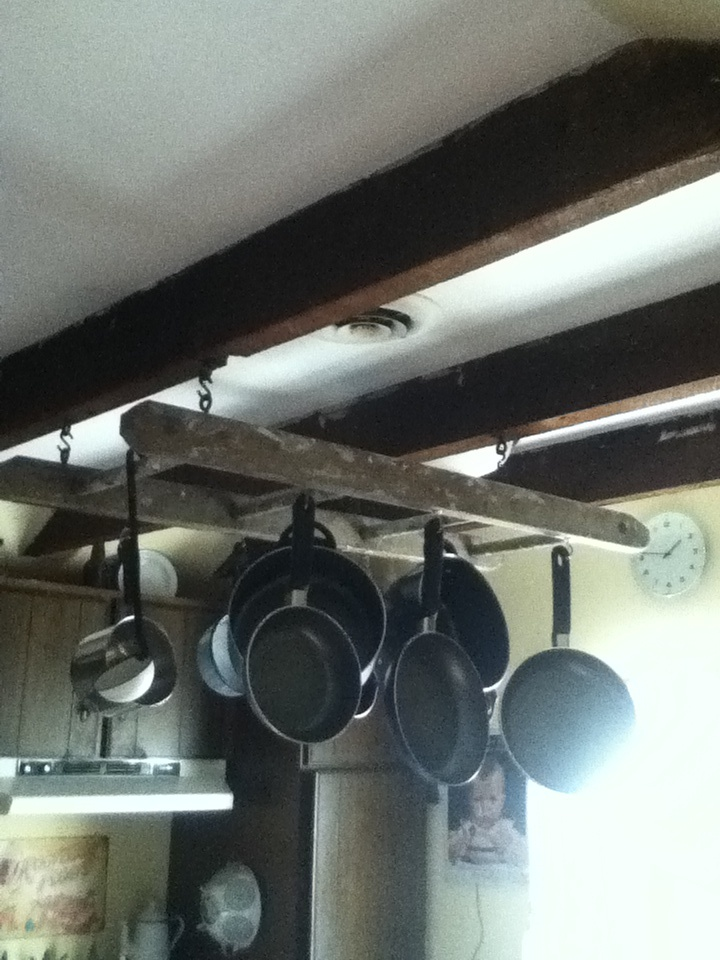 Diy pot rack super easy i took an old rung ladder and for Overhead pots and pans rack
