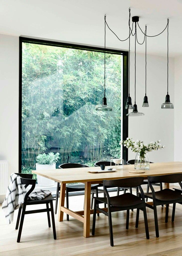 simple wooden table black dining chairs against a floor to ceiling window providing natural light inside a white interior scheme