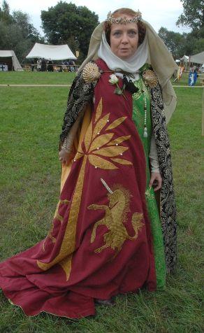 Vyšívaný půlený surcotte    Půlený surcot na Turnaj, zelená část z tkaniny se stromem a dvěma jeleny ve skoku v medailonech a na druhé části dva půlmetroví jednorožci ve skoku vyšití kladenou nití a strom je brokátová aplikace. Polovina 14. století.    Na další stránce najdete detail výšivky.