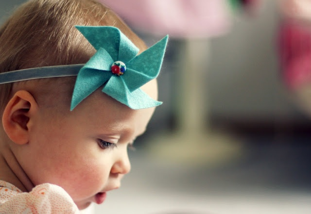 Handmade felt pinwheel tutorial. Here it is used to embellish an infant headband, but I could see it as a garland or decor embellishment!