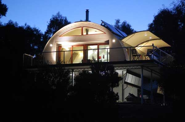 Convertible House: Two story dwelling on dusk with the operable awnings open and illuminated. What a beautiful image.