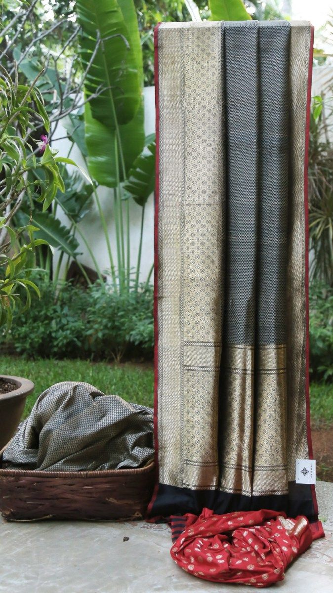 This iridescent Benares silk is in black with a pattern in beige. The border has an intricate weave in gold zari with a cherry red selvedge and is finished by an intricate weave on the pallu making...