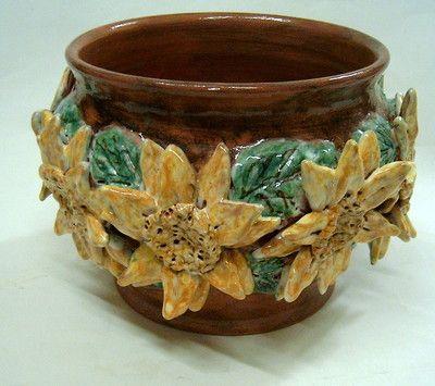 Bellissimo cache-pot in ceramica,foggiato al tornio e con 8 girasoli,modellati a mano e applicati al vaso.Artigianato italiano di qualità,pezzo unico pregevole e il cui valore aumenterà nel corso del tempo.Dimensioni del cache-pot.diametro 16cm altezza 14cm.Il ciliegio.Ilciliegio