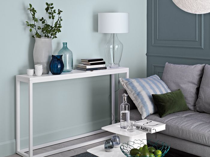 Salon skomponowany z odcieni błękitów pozwala wykreować wyjątkowe pomieszczenie pełne elegancji i subtelnego uroku. Szara sofa nabiera zupełnie nowego wyglądu jeżeli udekorujemy ją niebieskimi i zielonymi poduszkami. / Tikkurila Color Now - paleta FRESH (błękity i fiolety)