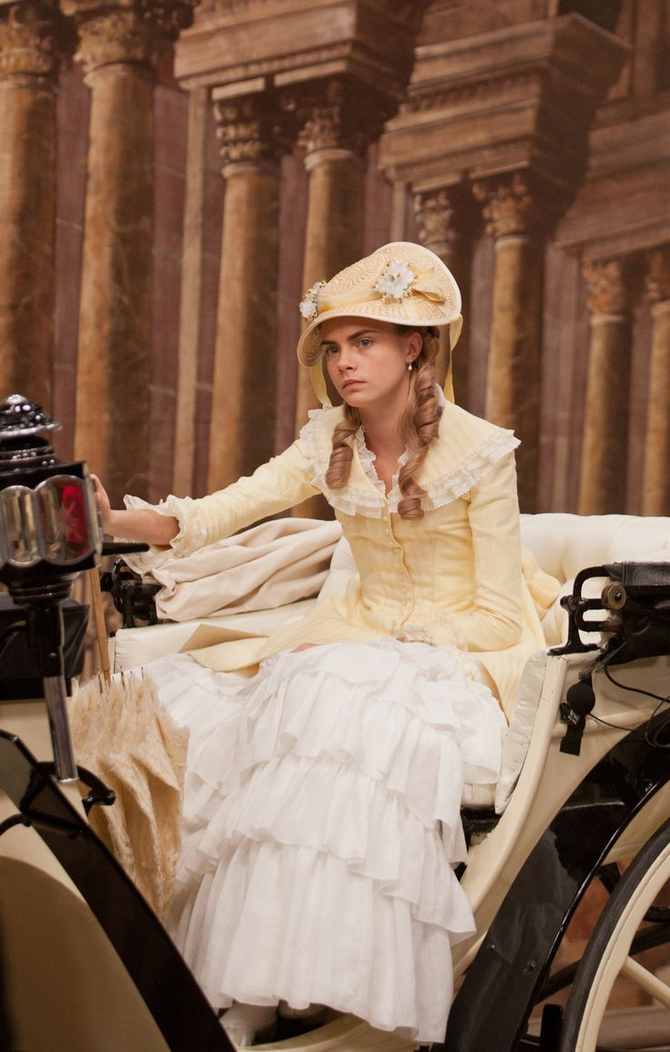 Anna Karenina - Cara Delevingne as Princess Sorokina wearing a pale yellow corseted dress with ruffled white skirt and lace details on the bodice. A lace parasol and a straw hat with ribbons and flowers complete the outfit.