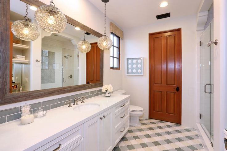 Large glass pendant lights and beautiful green and yellow tile work on the floor give this lovely bathroom a hint of exotic Mediterranean style. Otherwise, the design is kept fresh and simple.