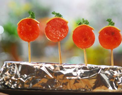 Watermelon roundels soaked in thickened orange juice, pierced with toothpicks and served topped with cheese slice.