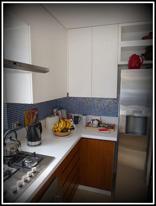 Cocina enchapada, con espacios aéreos para ocupar el máximo espacio. Cubierta Silestone, puertas con tirador oculto o en 45°.