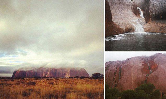 Tourists treated to rare sight as steady rainfall cascades down Uluru