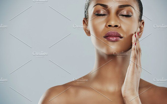Serene woman with closed eyes and touching cheek by Stefan & Janni on @creativemarket
