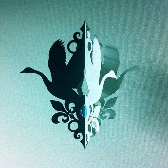 シリーズ:「バレエ」より、白鳥の湖のモビールです。「眠れる森の美女」・「くるみ割り人形」と共に三大バレエの一つと云われる、クラシックバレエの傑作「白鳥の湖 Swan Lake」。白鳥(オディット)と黒鳥(オディール)が、クルクル、フワフワと優雅に舞い踊ります。*白鳥と黒鳥の羽根の隙間が、向かい合うオディットとオディールの横顔になっています。素材:レザック紙・糸・ステンレス線サイズ:上段・・・・235mm × 180mm    下段・・・・(黒鳥/オディール)240mm × 200mm ・ (白鳥/オディット) 220mm × 150mm