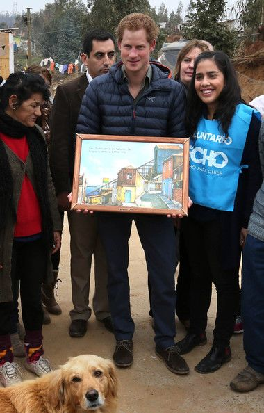 Prince Harry is given a gift as he is shown the devastation left by the Valparaiso fire that burnt down many homes in the poorest area of the town on June 28, 2014 in Valpariso, Chile.   Notice the doggie photo bomb
