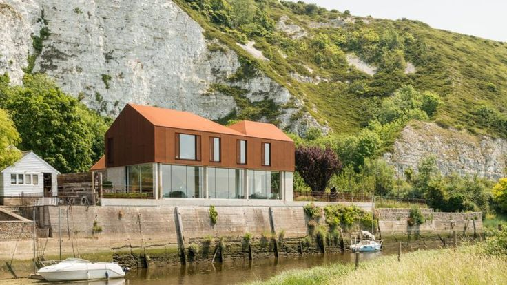 Designed by architect Sandy Rendel and completed in 2015, the home sits on the banks of the River Ouse in the South Downs National Park, right beneath Cliffe Hill.
