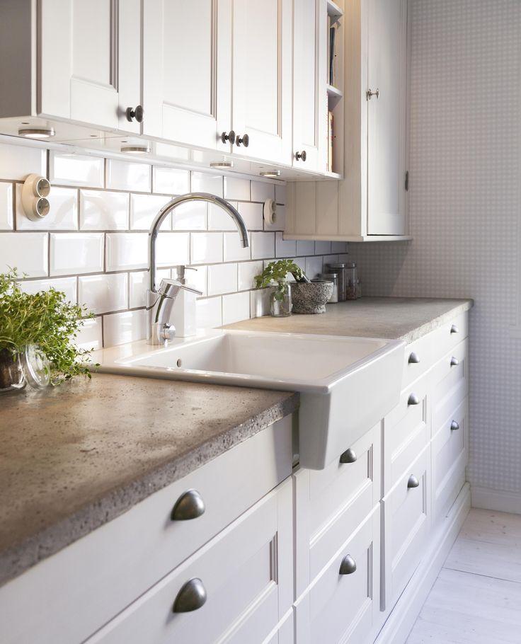 Concrete countertop in white kitchen.--i love these cabinets