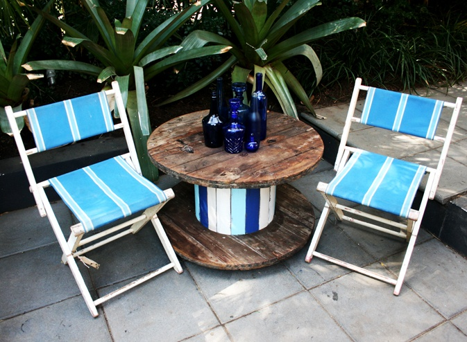 Industrial spool table with vintage striped canvas chairs.