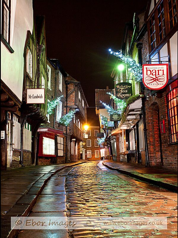 The beautiful Shambles in York at Christmas - after a rain shower the pretty lights cause an attractive glow on the cobbles