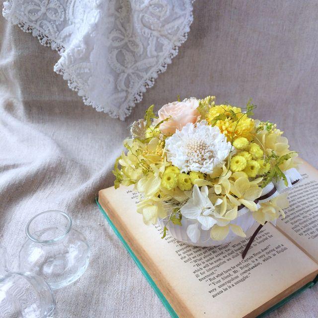 白にミルクティー色のラインが入ったカフェボールに、ふんわりアレンジ。優しく明るいお色の黄色で、Happyな贈り物にぴったりです。女性らしい優しさも表現したかったので、レース調のアイテムなどもプラスして、柔らかな雰囲気でお作りしています。◆プリザーブドフラ...