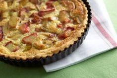 Rabarbertaart gebakken op een vel bladerdeeg, daarop rabarberstukjes en een beslag van zelfrijzende bloem, amandelpoeder, suiker, eieren en room