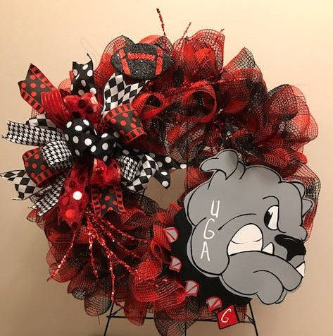 A fun Georgia Bulldog wreath. Uses red/black premium deco mesh. Sign was handmade with Georgia Bulldog with a growl face. Terri bow uses 6 different ribbons. 2 stems of glittered red whisps. 4.5 red/blk glittered football.