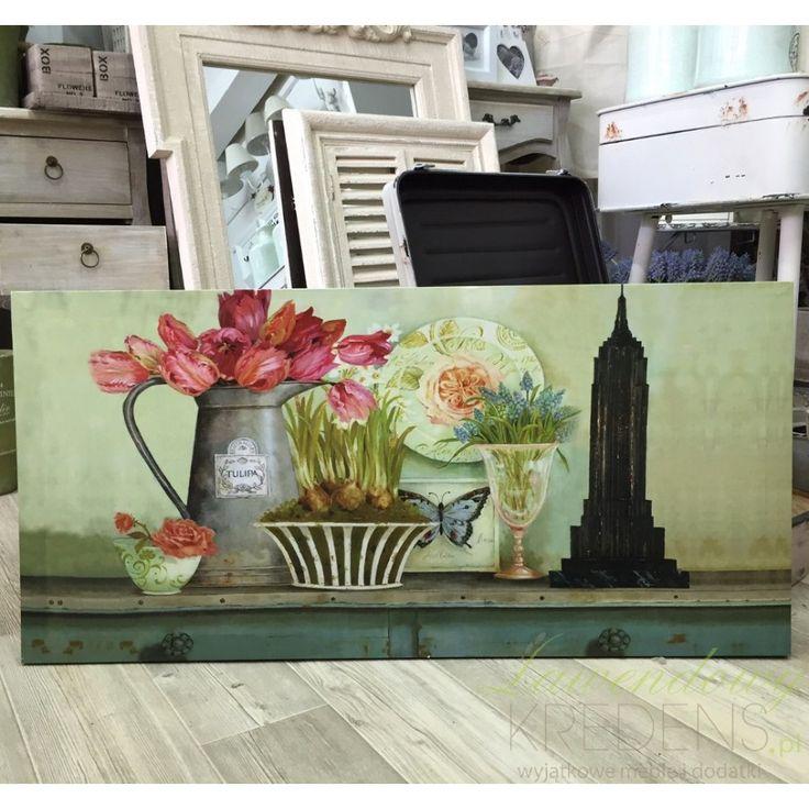 Piękny podłużny obraz w bardzo żywej kolorystyce przedstawiający kwiaty w różnych naczyniach, jest to motyw typowy dla prowansalskiego stylu.