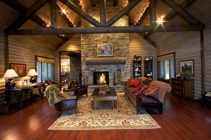 Katahdin Cedar Log Homes: Extreme-Makeover Oriental rug and more traditional furniture keep this from being overly stereotypical log lodge look to a wider audience.