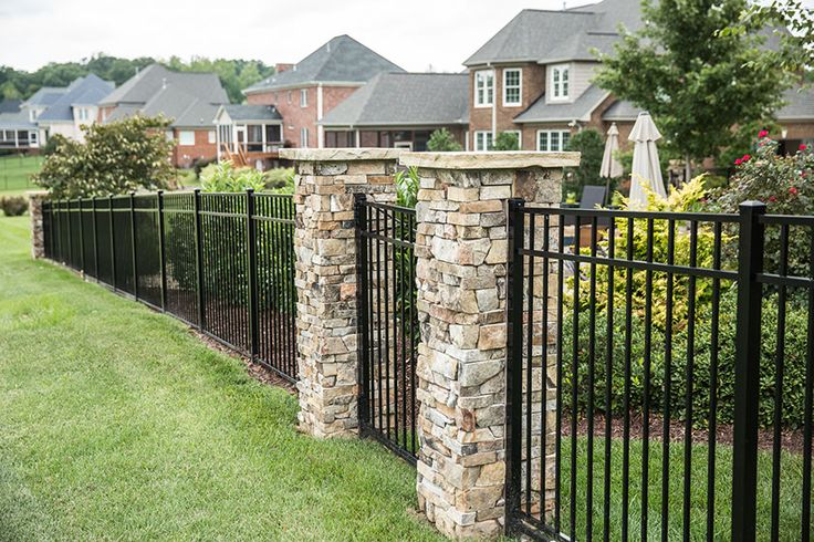 Custom Aluminum Fencing with custom built stone columns surrounding the gate access to this golf course home.