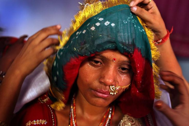 Fifteen-year-old Sarita's face, covered in tears and sweat, is covered before she is sent to her new home with her groom. The previous day, she and here young sister, Maya, 8, were married to another set of siblings on the Hindu holy day of Akshaya Tritiya, called Akha Teej in North India.