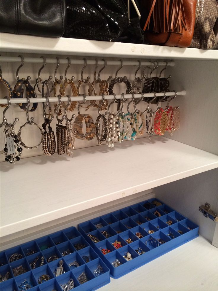 Jewellery storage: bracelets on a tension rods and shower hooks, earrings in a sewing storage tray
