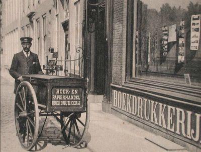 R.M.Smits in Middelburg: boekdrukkerij, boek- en papierhandel. Boven op de kar staat: leesinrichting. Omstreeks 1900