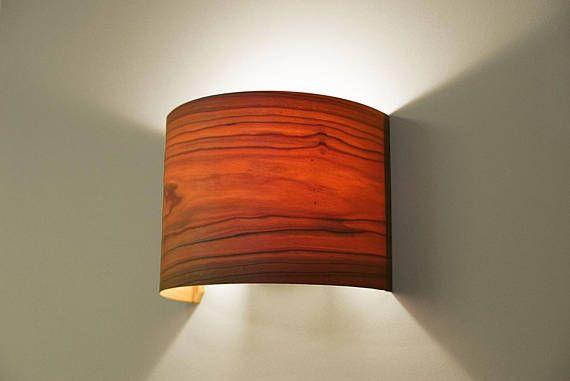 Eine halbkreisförmige Wandlampe, die die Maserung des Furniers voll zur Geltung kommen lässt. Die Lampe besteht aus einer weiß lackierten Basis aus Metall zur Befestigung an der Wand und einem Schirm aus Furnier. Einfacher Aufbau: Der Lampenschirm ist flach und biegsam, er wird mit Magneten an
