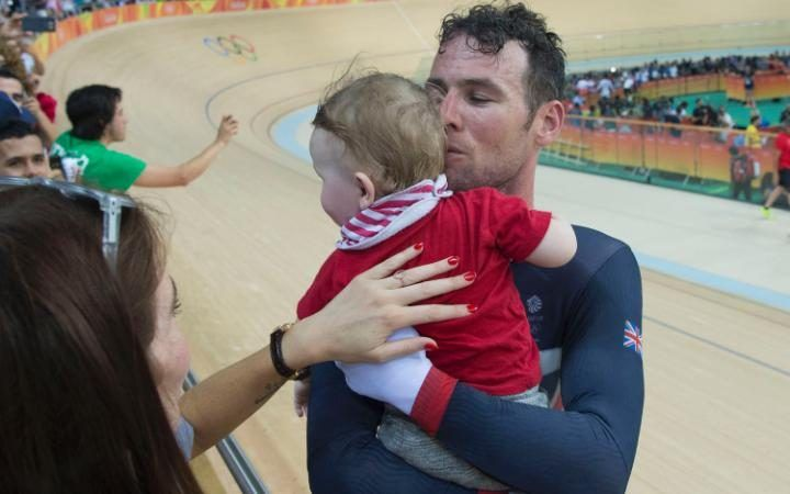 Britain's Men's Omnium rider Mark Cavendishgreets his wife and baby after…