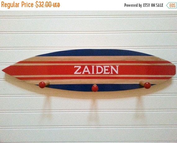 Wall Rack - Surfboard Rack - Surf Decor - Beach Decor - Surfer Decor - Wall Hooks - Beach House Decor - Surf Decor - Nautical Decor - Surf    Surf board measures 21 long x 5 wide. Unfinished wood with red stripes in middle and royal blue on the edges. Also has 3 large wooden pegs unpainted with red tips. Would be great to hang towels, keys or coats. Add something special to your beach themed room. We can paint this any color and with or without a name. Let us know and we will create…